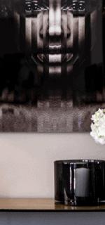 bord med blomst og dekorativt bilde på vegg